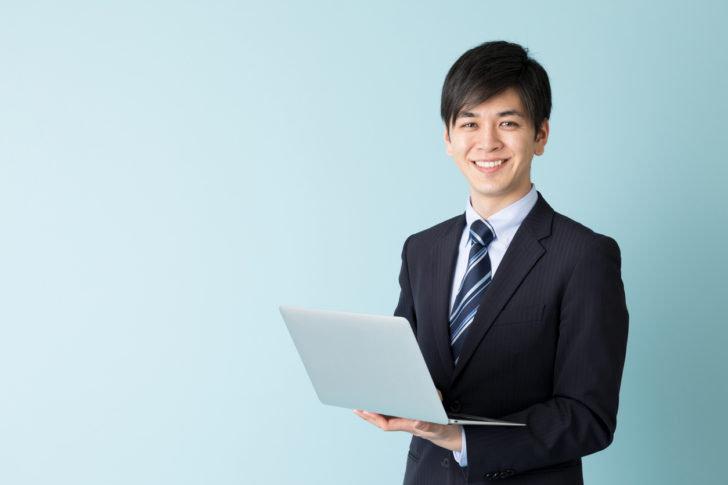 ノートパソコンを使うスーツの男性