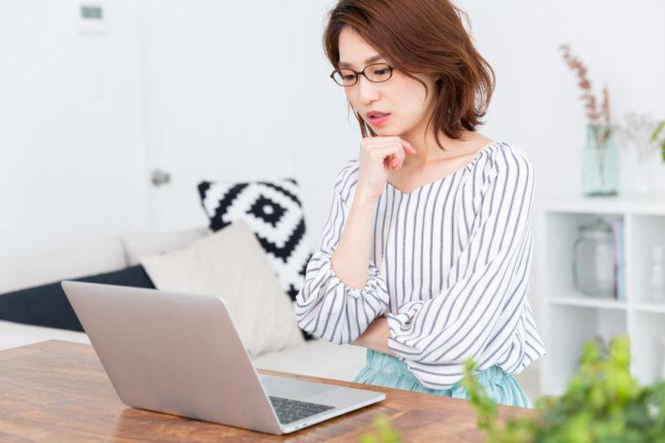 パソコンを使って考えている女性
