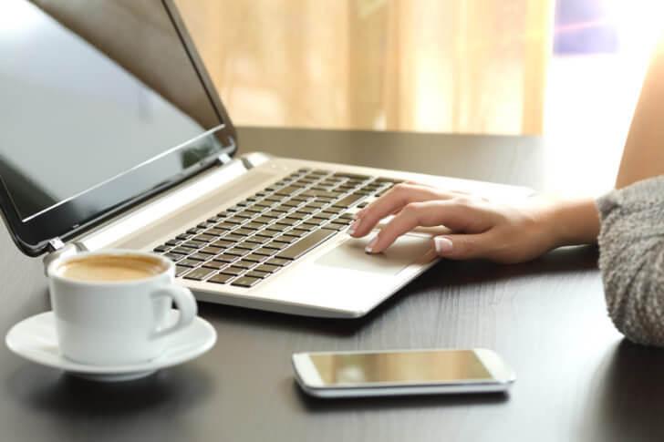 カフェでノートパソコンを使う女性
