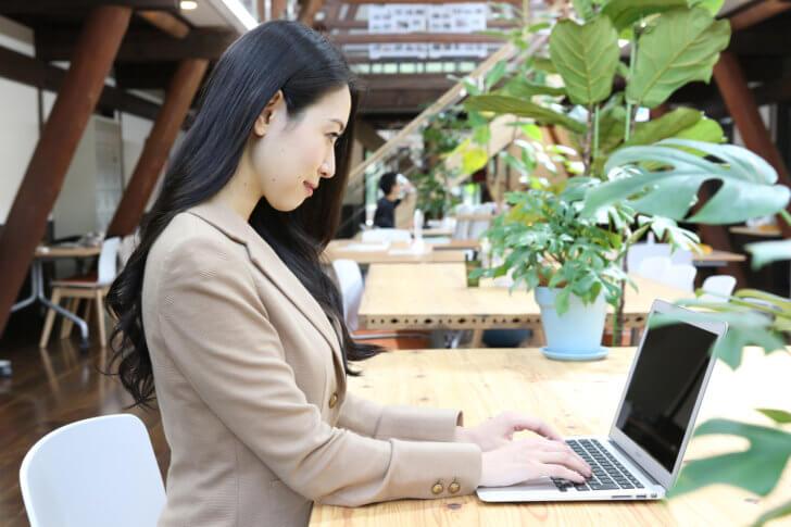 MacBookを活用するスーツの女性