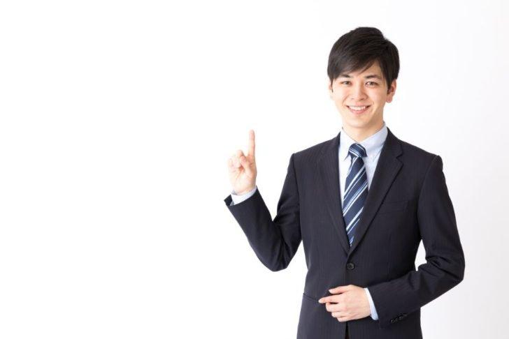 指を立てるスーツの男性