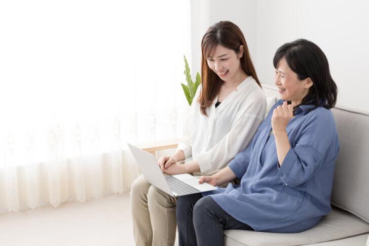 パソコンを開いて話をしている母と娘