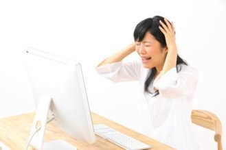 パソコンの電源が入らず困っている女性