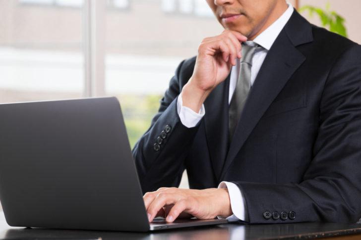 パソコンを操作しながら考え込む男性