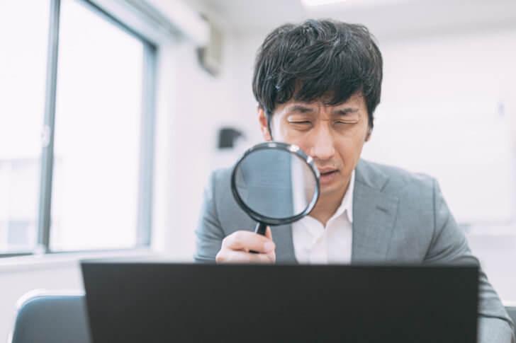 パソコンで困っているスーツの男性