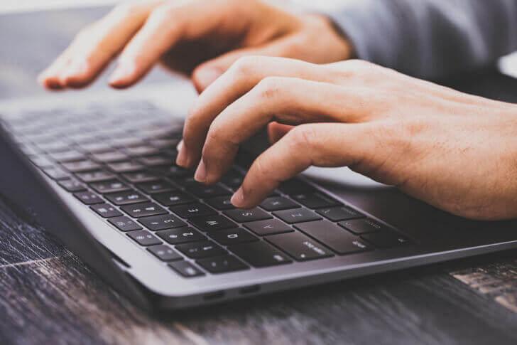 ノートパソコンのキーボードを打つ手